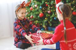 Happy children girls with christmas gifts near christmas tree in morning royalty free stock photo