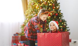 Happy children girls with christmas gifts near christmas tree in morning stock photography