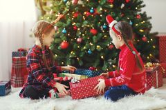 Happy children girls with christmas gifts near tree in morning stock photography