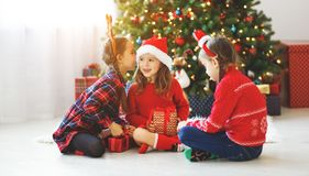 Happy children girls with christmas gifts near tree in morning stock photos