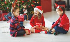 Happy children girls with christmas gifts near tree in morning royalty free stock image