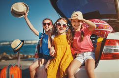 Happy children girls friends sisters on the car ride to summer trip royalty free stock photos