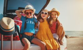 Happy children girls friends sisters on the car ride to summer trip royalty free stock photo