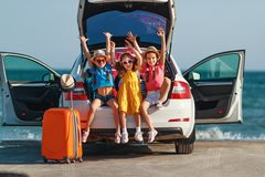 Happy children girls friends sisters on the car ride to summer trip stock image