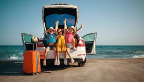 Happy children girls friends sisters on the car ride to summer trip stock images