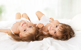 Happy children girls twin sisters in bed Stock Photography