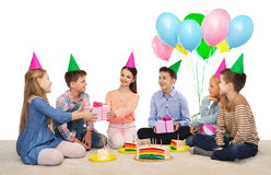 Happy children giving presents at birthday party Royalty Free Stock Images