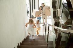 Happy children going upstairs, family with boxes moving in house. Happy children going upstairs inside two story big house, excited kids having fun stepping royalty free stock images