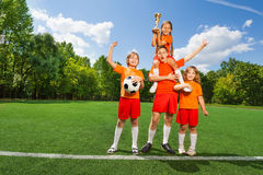Happy children with golden cup stand in pyramid Stock Photo