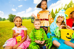 Happy children in Halloween costumes sit on grass Royalty Free Stock Photos