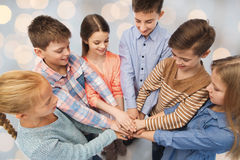 Happy children with hands on top over lights Royalty Free Stock Photo