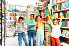 Happy children with hands up hold exercise books. Happy excited children with hands up with exercise books in the library Royalty Free Stock Photo