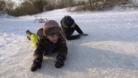 Happy children happily floating on a frozen lake. Together they rejoice and be glad in natural rink. A beautiful sunny stock video footage