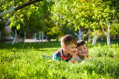 Happy children having fun outdoors. Kids playing in summer park. Little boy and his brother laying on green fresh grass holiday ca royalty free stock image