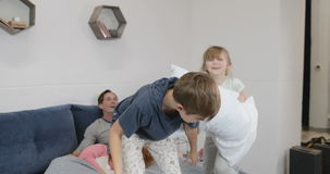 Happy children having fun in parents bedroom fighting pillows in morning while mother and father lying pn bed laughing stock footage