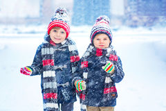Happy children having fun with snow in winter. Two little kid boys in colorful clothes playing outdoors during snowfall. Active leisure with children in winter royalty free stock photography