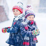 Happy children having fun with snow in winter. Two little kid boys in colorful clothes playing outdoors during snowfall. Active leisure with children in winter royalty free stock image