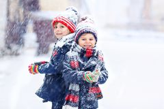 Happy children having fun with snow in winter. Two little kid boys in colorful fashion clothes playing outdoors during strong snowfall. Active leisure with stock image