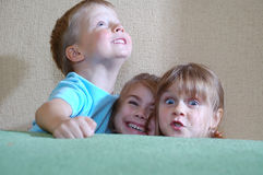 Happy children hiding behind the sofa Stock Photography
