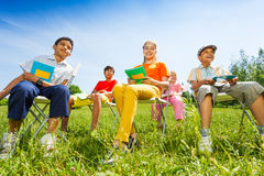 Happy children hold exercise books and sit Royalty Free Stock Photos