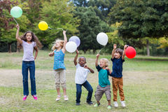 Happy children holding balloons Royalty Free Stock Photography
