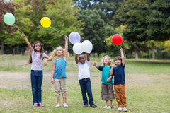 Happy children holding balloons Stock Images