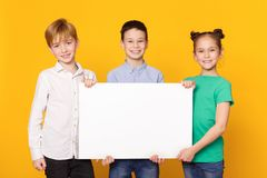 Happy children holding blank banner for advertisement. Against yellow background stock photos
