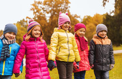 Happy children holding hands in autumn park Royalty Free Stock Photos