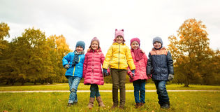 Happy children holding hands in autumn park Stock Image