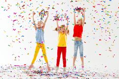 Happy children on holidays  jumping in multicolored confetti on Royalty Free Stock Photos