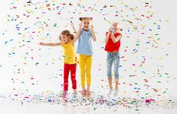 Happy children on holidays jumping in multicolored confetti on Royalty Free Stock Photography