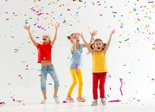 Happy children on holidays  jumping in multicolored confetti on Royalty Free Stock Photo