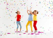 Happy children on holidays  jumping in multicolored confetti on Stock Photos