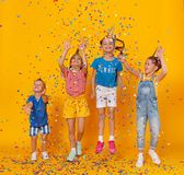 Happy children on holidays  jumping in multicolored confetti on yellow royalty free stock images