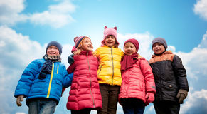 Happy children hugging over blue sky background Royalty Free Stock Photos