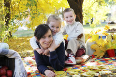 Happy children hugging their mother under autumn trees Royalty Free Stock Photography