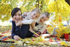 Happy children hugging their mother under autumn trees Royalty Free Stock Photos
