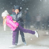Happy children ice skating at ice rink outdoor, figure skating stock image