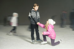 Happy children ice skating at ice rink, winter night. Happy children ice skating at ice rink outdoor, at winter snowy night. Brother helps for his sister. Sport stock photography
