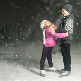 Happy children ice skating at ice rink, winter night Royalty Free Stock Image