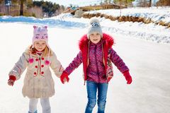 Happy children ice skating on an ice rink outdoors. Sport and a healthy lifestyle. Funny kids, they are sisters and girlfriends.  stock photography