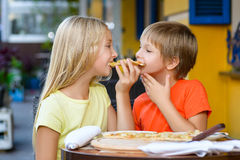 Happy children indoors eating pizza smiling Royalty Free Stock Image