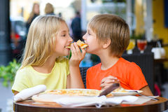 Happy children indoors eating pizza smiling Royalty Free Stock Images