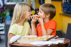 Happy children indoors eating pizza smiling. Happy little children indoors eating pizza smiling Royalty Free Stock Photography