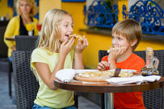 Happy children indoors eating pizza smiling Stock Images