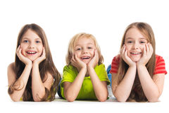 Happy children isolated on white. Happy smiling three children in colorful clothes laying on floor isolated on white background stock photos