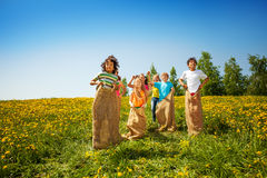 Happy children jump in sacks on green meadow Royalty Free Stock Photo