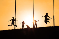 Happy children jumping. Silhouettes of happy children jumping on top of the hill in sunset Royalty Free Stock Image