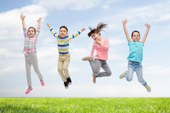 Happy children jumping in air over sky and grass. Happiness, childhood, freedom, movement and people concept - happy little children jumping in air over blue sky Stock Images