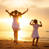 Happy children jumping on the beach. On the dawn time Stock Image